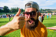canvas print picture - Top list summer festival must visit. Highly recommend top list. Hipster visiting event picnic fest or festival. Man cheerful face shows thumb up. Man bearded in front of crowd riverside background