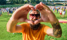 Man Bearded Hipster In Front Of Crowd People Show Heart Gesture Riverside Background. Hipster Happy Celebrate Event Picnic Fest Or Festival. Urban Event Celebration. Cheerful Fan Love Summer Fest