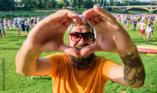 Stampa su Tela Man bearded hipster in front of crowd people show heart gesture riverside background