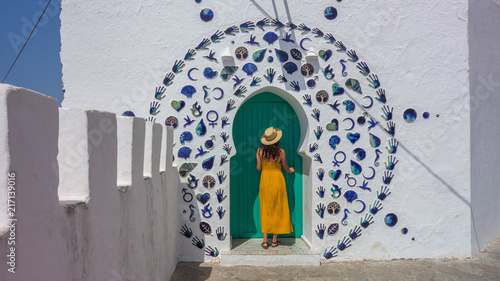 Woman in yellow dress and hat in a nice decorated door of the village of Asilah in Morocco