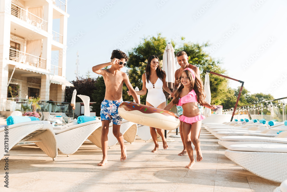 Fototapety, obrazy: Image of happy caucasian family with children resting near luxury swimming pool, with white fashion deckchairs and umbrellas outside hotel