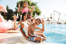 Image Of Attractive Caucasian Family With Children Sitting Near Luxury Swimming Pool, With Pink Rubber Ring Outside Hotel