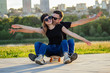 active couple in love hugging in the summer park. beautiful woman and man have fun with a skateboard(longboard) background of a sunset by the river. guy and girl date. romance flirting concept