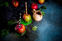 Traditional Autumn Delicacy, Apples In Caramel Glaze. On A Dark Background, With Apples, Leaves, Caramel Sauce And A Warm Blanket. Copy Space For Text