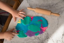 Close Up Of Girl's Hand With Clay And Rolling Pin On Table