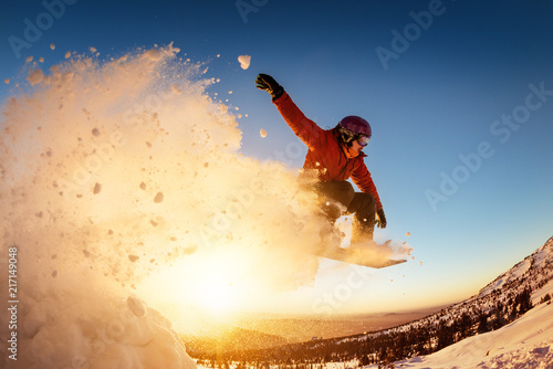 Valokuva Snowboarder jumps sunset with snow dust