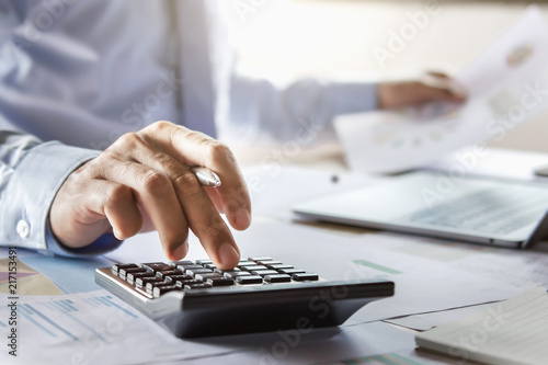 Obraz accountant working on desk using calculator for calculate finance report in office - fototapety do salonu