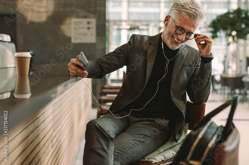 Mature businessman at cafe listening music from cellphone - 217154052