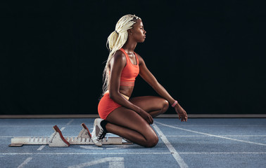 Woman sprinter sitting at the start line on a running track
