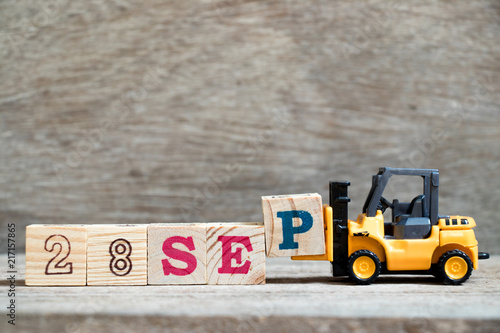 Fotografia  Toy forklift hold block P to complete word 28 sep on wood background (Concept fo