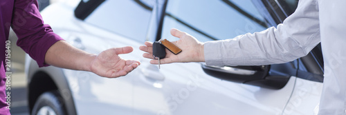 Cuadros en Lienzo  Panorama and close-up of car seller's hand with keys and buyer's hand after tran