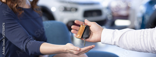 Panorama and close-up of car dealer's hand giving keys to buyer