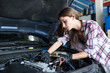 Young woman in checkered shirt working with car engine on repair station in daylight