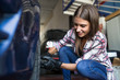 Young casual woman wearing gloves and screwing wheel of car working in repair shop