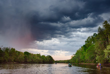 Three Kayakers Paddle A River Before A Storm