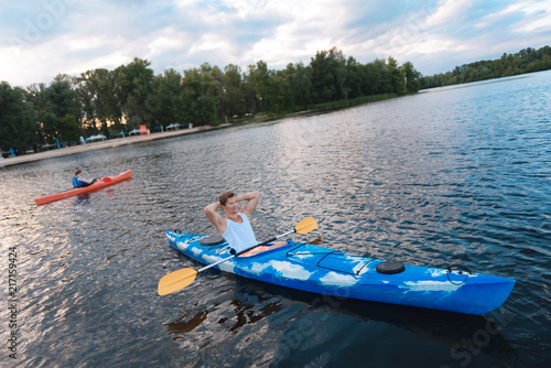 Relaxed man. Blonde-haired strong muscle man feeling very relaxed while sitting in canoe