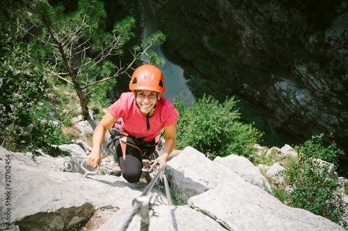 Young happy woman who is climbing along a via ferrata