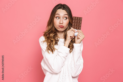 Portrait of a pensive young woman holding chocolate bar Fototapet