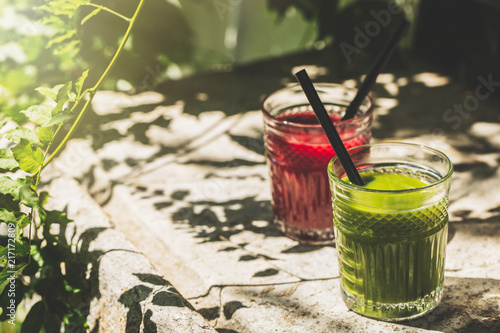 Fotomural Red and green detox juice glass  with copy space in a sunny outdoors