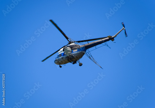 A helicopter of agricultural aviation is flying in the blue sky.