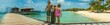 Two kids standing on a Pier looking over the Caribbean Sea, White Sand Beach with Blue Sky and Coconut Trees Oranjestad, Aruba