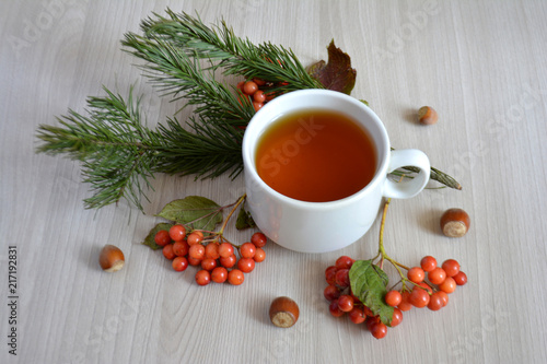 Staande foto Thee A Cup of hot tea, berry, fir branch on the table. Autumn or winter warming drink. Autumn concept