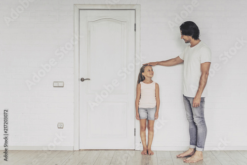 Fototapeta Smiling Father Measuring Height of Cute Daughter.