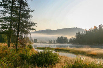 Fototapeta na wymiar Sunrise with fog on the water at Oxbow Bend in Grand Teton National Park, Wyoming