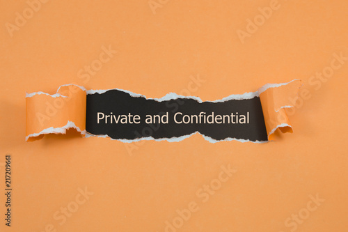 Fotomural The word Private and confidential appearing behind torn paper.