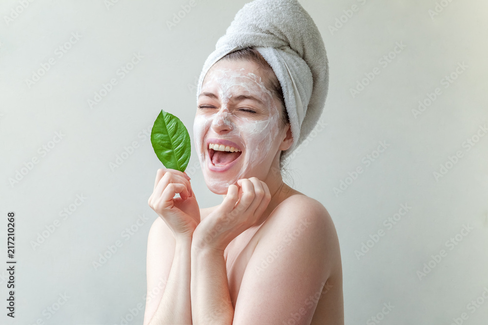 Fototapeta Beauty portrait of a smiling brunette woman in a towel on the head with white nourishing mask or creme on face and green leaf in hand on white background isolated. Skincare cleansing eco organic