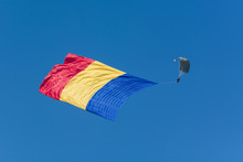 A Parachutist Unveiling The Flag Of Romania At An Airshow