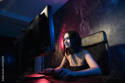 Concerned girl gamer in headphones playing network games preparing to participate in international competitions in e-sports Canvas Print