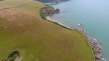 4K Cornwall Aerial Over Par Sands Beach And Surrounding Coast And Polkerris Harbour And Beach. Flying Over Fields With Sheep And Cows With Lush Green Grass Along The South West Coast Path.
