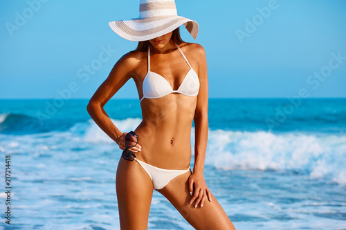 Obraz Portrait of sexy beautiful tanned woman posing in colorful swimwear bikini at the sea coast. Exotic country travel and rest concept. Slim figure and sexy body. - fototapety do salonu