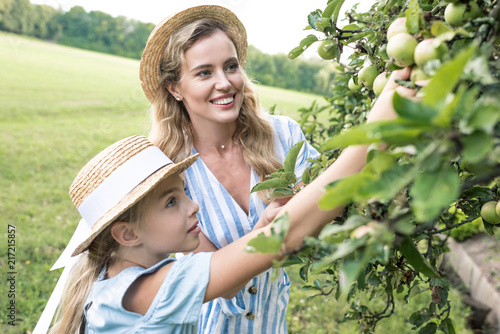 happy mother and daughter picking apples together Fototapeta