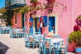 Fototapeta Uliczki - Traditional greek vivid lilac colored tavern on the narrow Mediterranean street on hot summer day