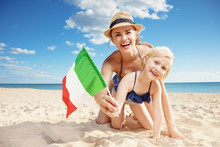 Happy Modern Mother And Daughter On Beach Showing Italian Flag