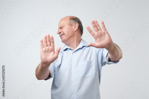 Fotografía  Displeased mature man refusing, stretching hands to camera over grey background