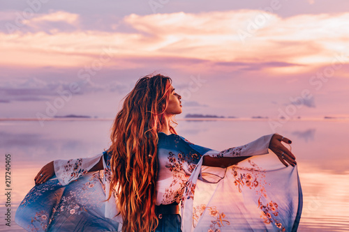 Fototapeta premium piękna młoda kobieta w eleganckiej sukni na plaży o zachodzie słońca