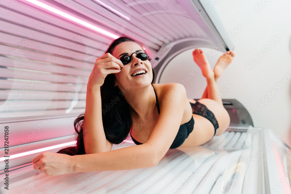 Photo  a slender sexy brunette girl lies in a horizontal tanning bed in protective glas