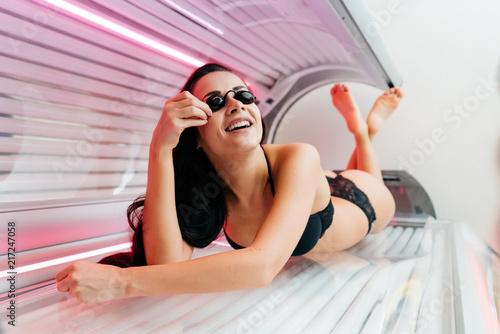 Obraz a slender sexy brunette girl lies in a horizontal tanning bed in protective glasses, wants an even tan - fototapety do salonu