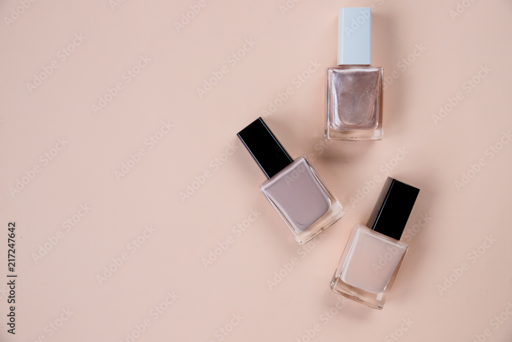 Fototapety, obrazy: Creative flat lay of fashion bright nail polishes on a beige background. Minimal style. Copy space. Beauty blogger concept. Top view. Nude tones.