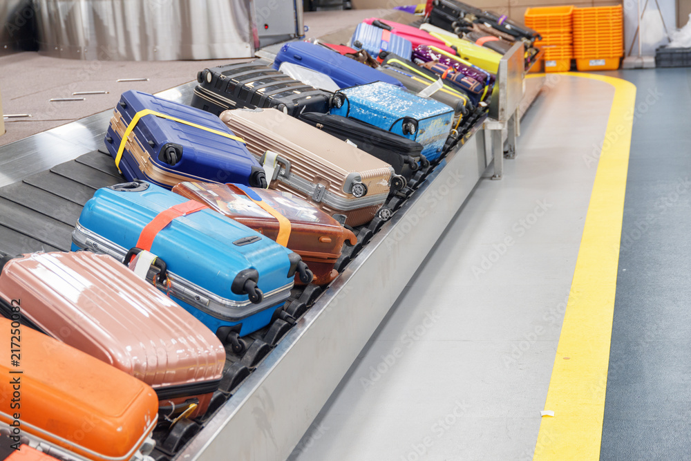 Fototapeta Bright suitcases and bags on luggage conveyor belt in airport