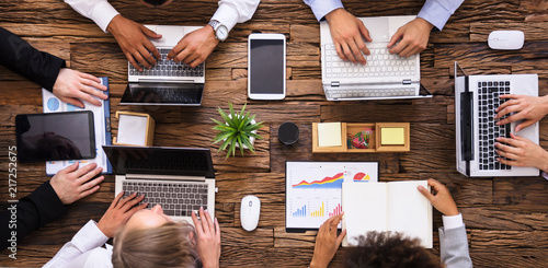 Group Of Businesspeople Working On Laptop