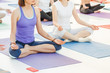 Group of happy cute young women sitting and stretching in yoga asana poses, meditation and workout training concept