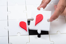 Man Connecting Broken Heart With Jigsaw Puzzle