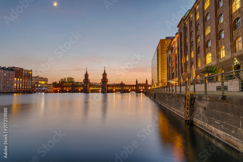 Fotobehang Centraal Europa The banks of the river Spree in Berlin with the Oberbaum Bridge in the back after sunset