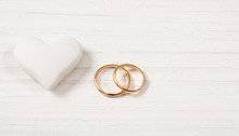 Close Up View Of Golden Wedding Rings And A White Heart, Isolated, Copy Space, On A White Wooden Background.
