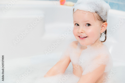 little girl have fun in the bath with soap on head #217271404