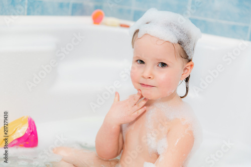 little girl washing herself at bath with soap on head #217271430